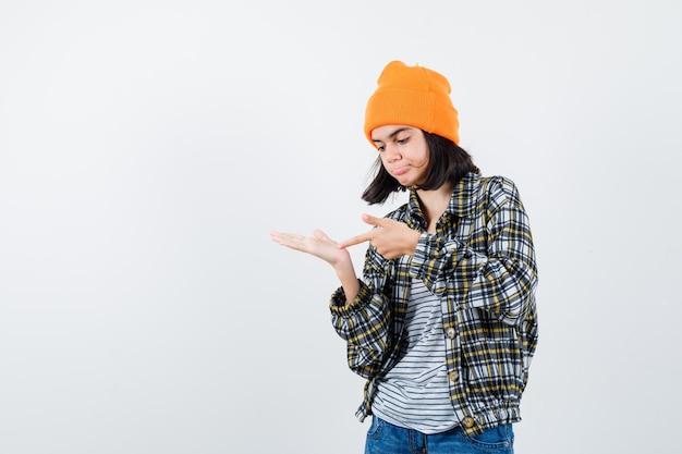 Kleine vrouw wijzend op palm in t-shirt en jas en muts die aarzelend kijkt