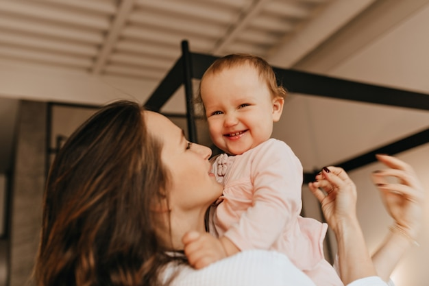 Kleine vrouwelijke baby lacht en kijkt naar de camera terwijl moeder haar knuffelt en haar in de armen houdt.