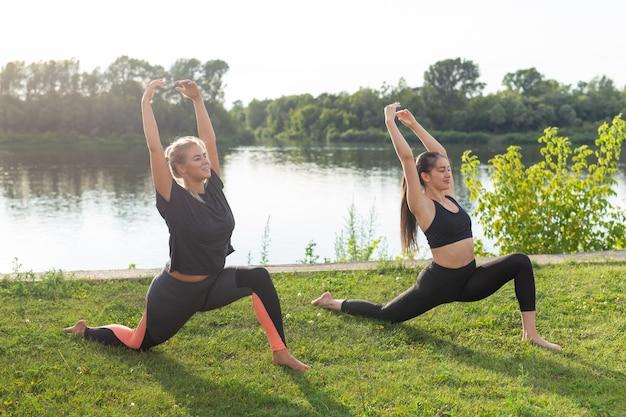 Kleine vrouwelijke fitnessgroep die op een zonnige dag yoga in het park doet