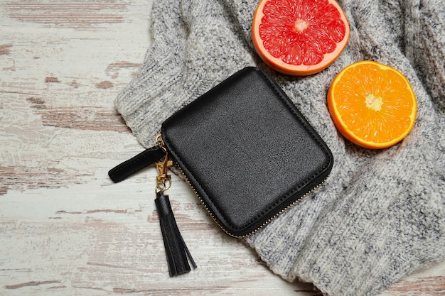 Kleine vrouwelijke zwarte tas en citrusvruchten op een trui