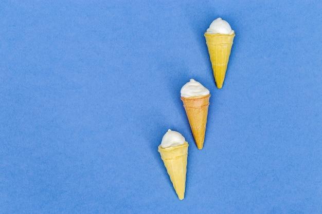 Kleine wafel kegels met ijs op papier achtergrond met kopie ruimte. bovenaanzicht. plat liggen. minimaal concept