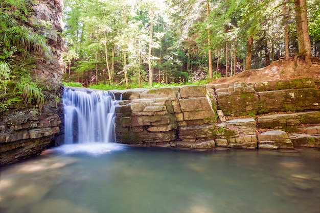 Kleine waterval in bergbos met zijdeachtig schuimend water