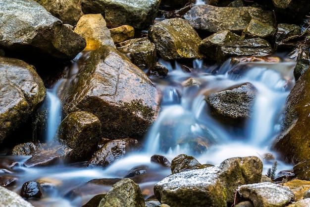 Kleine waterval met blauw schuimend water op natte stenen