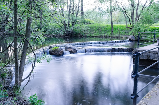 Kleine waterval op een kleine pittoreske beek in het bos