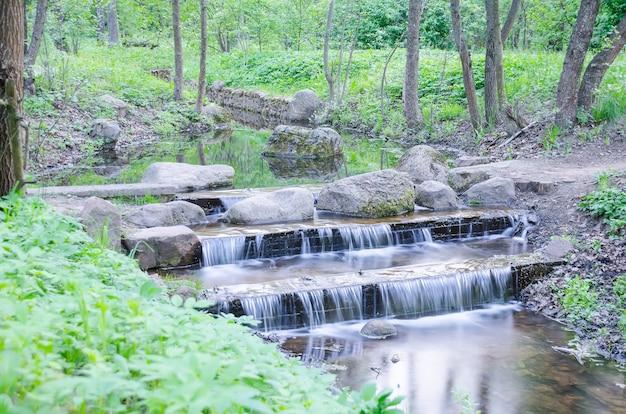 Kleine waterval op een kleine schilderachtige beek in het bos