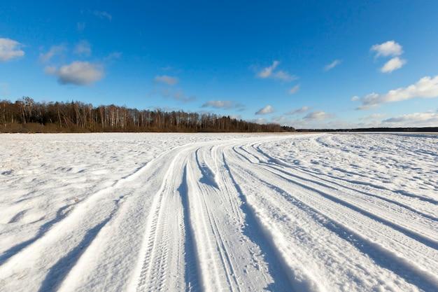 Kleine weg in de winter met sporen van autobanden. op de grond is er sneeuw na sneeuwval. blauwe lucht op de achtergrond