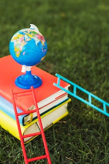 Kleine wereldbol die bovenop boekenstapel wordt geschikt