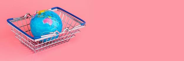 Kleine wereldbol in een winkelwagentje op een roze achtergrond