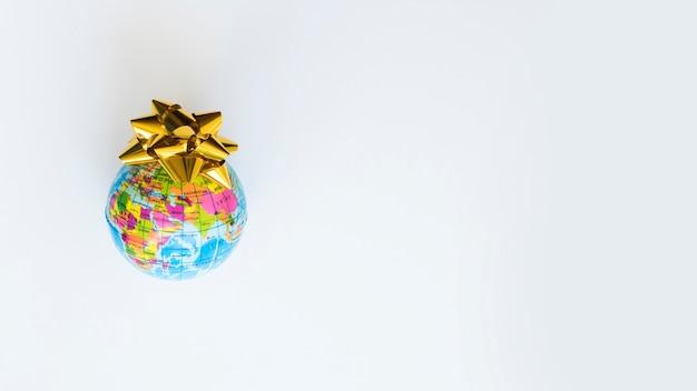 Kleine wereldbol met gele strik op tafel