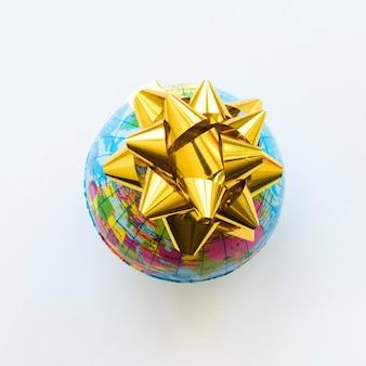 Kleine wereldbol met gele strik