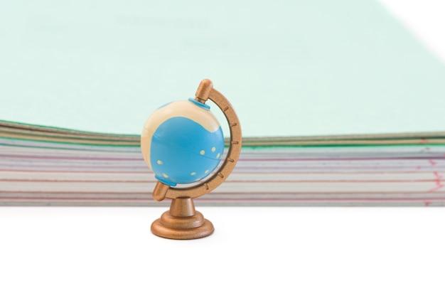 Kleine wereldbol op de achtergrond van schoolnotitieboekjes