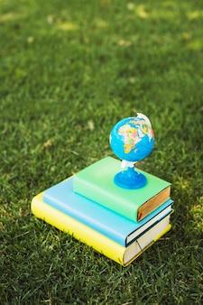 Kleine wereldbol samengesteld op stapel boeken