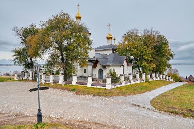 Kleine witstenen orthodoxe kerk met gouden baden aan de oever van de rivier. kazan