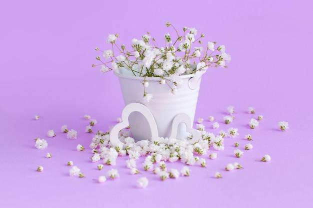 Kleine witte bloemen en harten op een lavendel achtergrond close-up