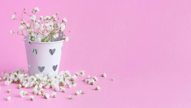 Kleine witte bloemen in een emmer op een roze achtergrond close-up