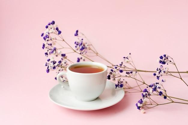 Kleine witte gypsophila bloemen op een roze pastel achtergrond met een kopje thee, ruimte voor tekst