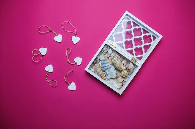 Kleine witte houten harten en witte houten doos met zeeschelpen binnen op roze achtergrond met exemplaarruimte. de dagkaart van heilige valentine op roze achtergrond.