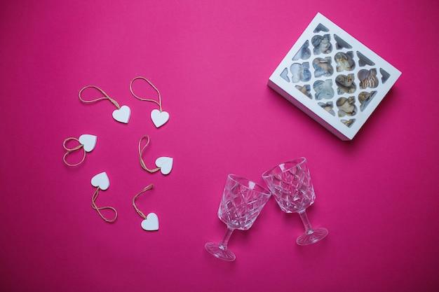 Kleine witte houten harten en witte houten juweel-doos op roze achtergrond met exemplaarruimte. de dagkaart van heilige valentine met twee wijnglazen op de roze achtergrond.