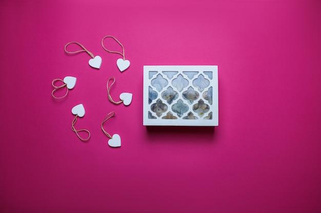 Kleine witte houten harten en witte houten juweel-doos op roze achtergrond met exemplaarruimte. de dagkaart van heilige valentine op roze achtergrond.
