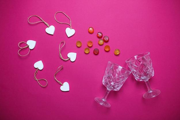 Kleine witte houten harten met twee wijnglazen en kleurrijk suikergoed op roze achtergrond met exemplaarruimte.