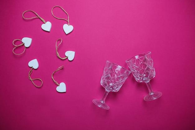 Kleine witte houten harten met twee wijnglazen op roze achtergrond met exemplaarruimte.