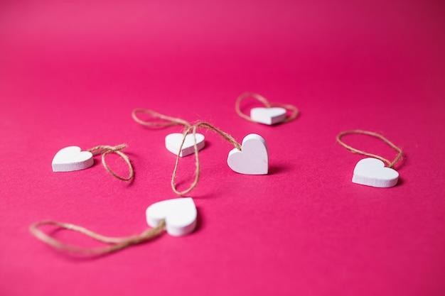 Kleine witte houten harten op roze achtergrond met exemplaarruimte. de dagkaart van heilige valentine op roze achtergrond.