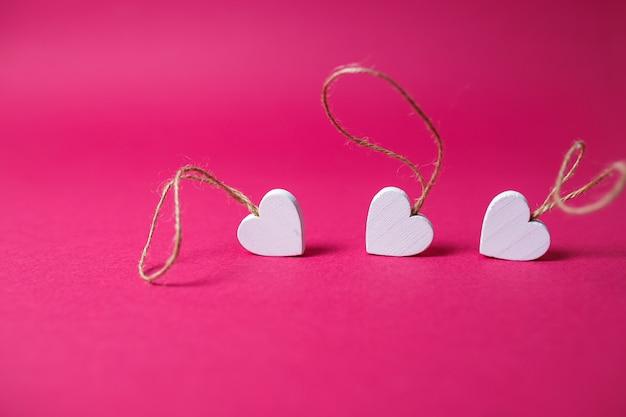 Kleine witte houten hartenmacro op roze achtergrond met exemplaarruimte. de dagkaart van heilige valentine op roze achtergrond.