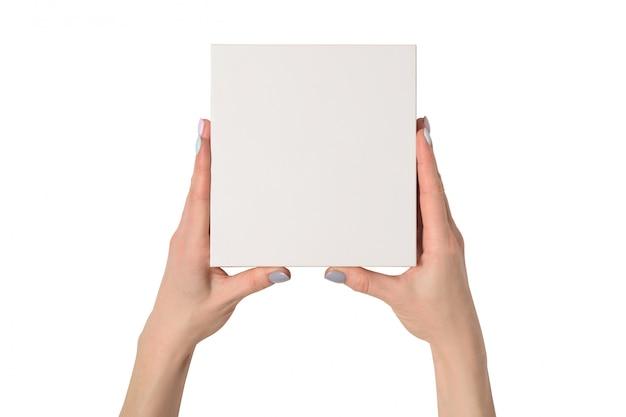 Kleine witte kartonnen doos in vrouwelijke handen. bovenaanzicht. isoleren