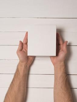 Kleine witte kartonnen dozen in mannelijke handen. bovenaanzicht. witte tafel op de achtergrond