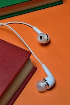 Kleine witte koptelefoon en een stapel boeken op een oranje achtergrond.