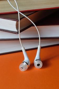 Kleine witte koptelefoons van de telefoon liggen op een stapel boeken op een oranje achtergrond.