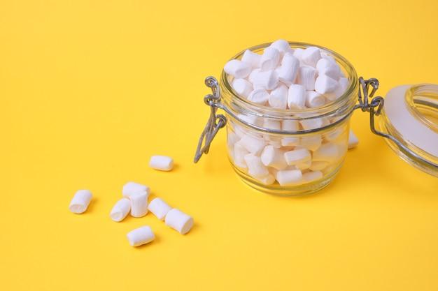 Kleine witte marshmallows in een pot op een gele achtergrond kopie ruimte