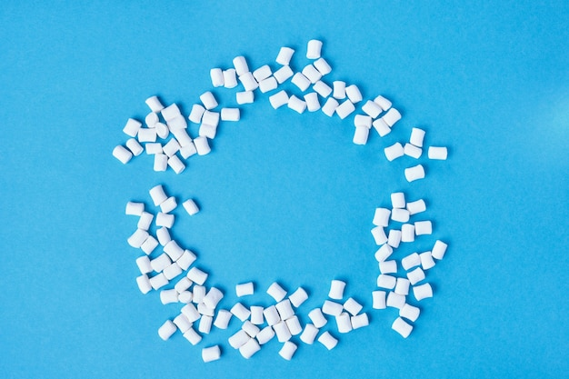 Kleine witte marshmallows verspreid over een blauwe achtergrond, cirkel van marshmallows bovenaanzicht