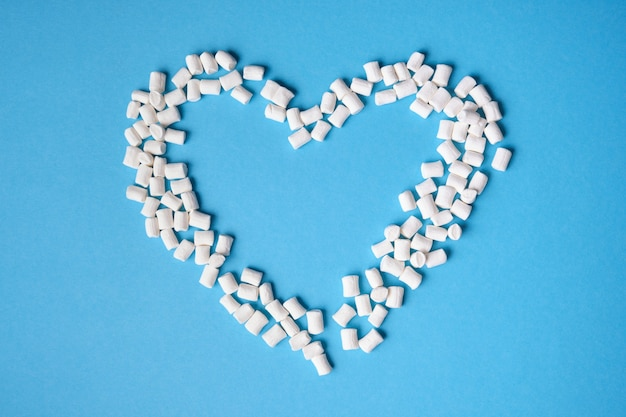 Kleine witte marshmallows verspreid over een blauwe achtergrond, hart van marshmallows bovenaanzicht