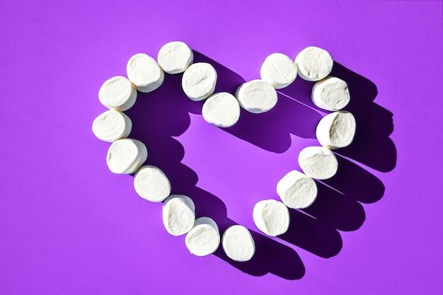 Kleine witte marshmallows verspreid over een blauwe achtergrond met kopieerruimte, hart van marshmallows bovenaanzicht mock-up. valentijnssnoepjes