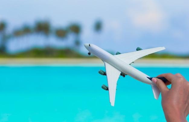 Kleine witte miniatuur van een vliegtuig op strand