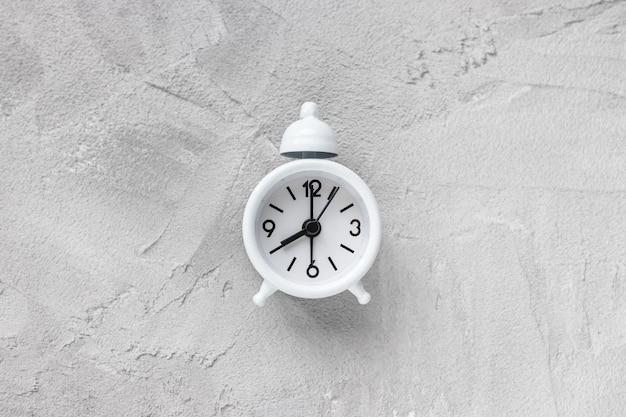 Kleine witte vintage wekker met bel op grijze achtergrond. ochtendtijd, kopieer ruimte