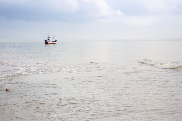 Kleine woden vissersboot liet het anker vallen bij de kustlijn.