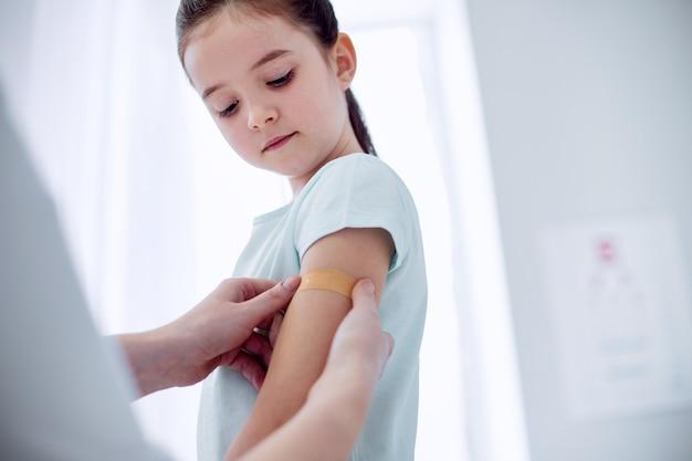 Kleine wond. lage hoek van gericht geconcentreerd meisje poseren op lichte achtergrond en naar beneden te kijken terwijl arts patch tegen haar arm te drukken