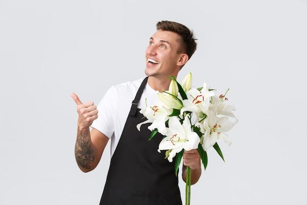 Kleine zakelijke detailhandel en werknemers concept knappe bloemistverkoper in bloemenwinkel die naar boven wijst