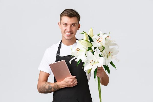 Kleine zakelijke detailhandel en werknemers concept knappe bloemistverkoper van bloemenwinkel die boeketten overhandigt