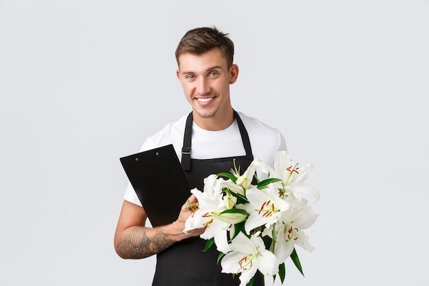 Kleine zakelijke detailhandel en werknemers concept knappe verkoper bezorger van bloemenwinkel met ...