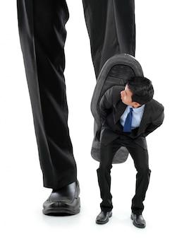 Kleine zakenman wordt verpletterd door de voeten