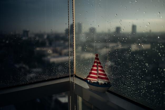Kleine zeilboot aan de rand van regenachtige ramen.