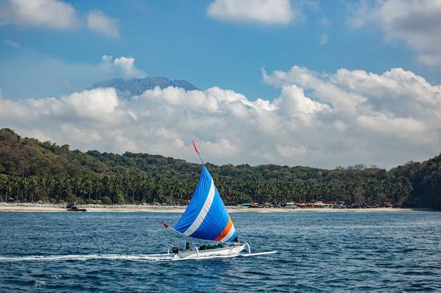 Kleine zeilboot drijft op water met geweldig uitzicht op de bergen.