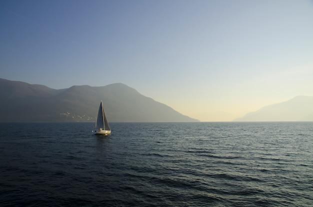 Kleine zeilboot in het meer met de zonsondergang