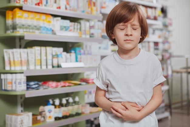 Kleine zieke jongen bij de apotheek