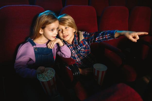 Kleine zus en broer kijken naar een film in de bioscoop