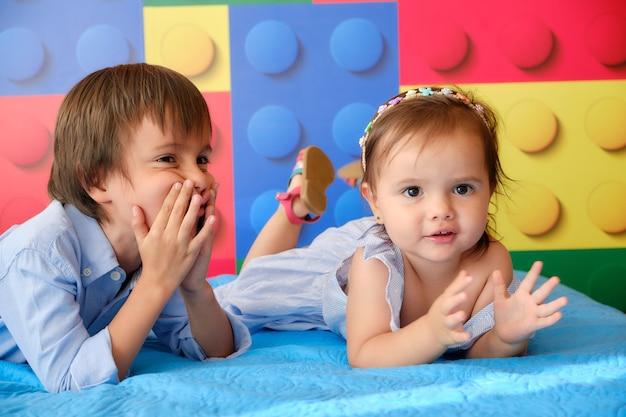 Kleine zus en broer liggen in het bed van hun kamer, plezier maken op een zomerse dag.