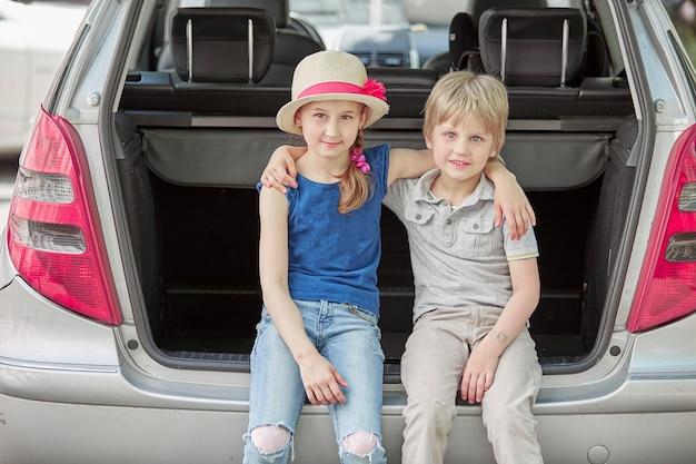 Kleine zus en broer zitten in de kofferbak van een auto met koffers. het concept van gezinsreizen
